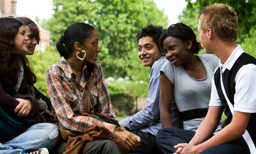A group of young people sitting together talking